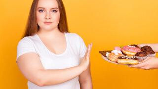 Frau lehnt Teller mit süßen Kuchen ab