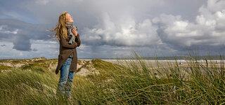 Junge Frau steht in den Dünen