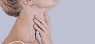 Frau fasst sich an den Hals
