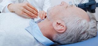 Ärztin untersucht Patienten am Hals