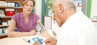 Frau in der Apotheke beim Blutdruck messen