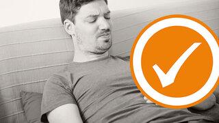 Mann mit Magenschmerzen liegt auf der Couch