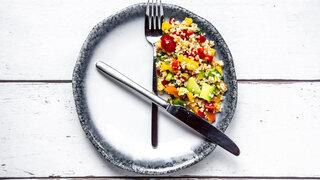 Intervallfasten: Teller und Besteck als Uhr mit Bulgursalat
