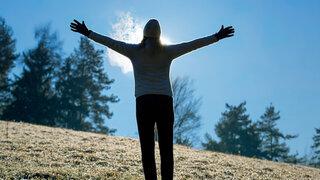 Silhouette einer Frau, die ihre Arme in die Höhe streckt