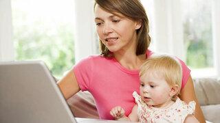 Mutter mit Kleinkind auf dem Schoß am Laptop