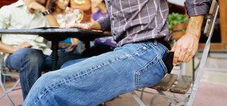 Mann holt seine Geldbörse aus der Hosentasche