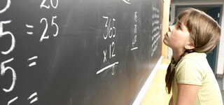 Schülerin rechnet an Tafel