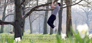 Corona-Krise, Leute treiben an der frischen Luft Sport im Volkspark Friedrichshain Mann Baum Kraftsport
