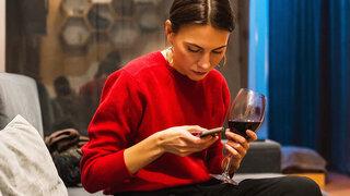 Coronavirus Alkohol zuhause Trinken Wein Frau Handy Smartphone Konsum gestiegen Wohnzimmer