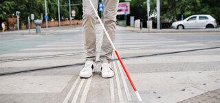 Sehbehinderter Mann läuft über die Straße