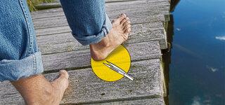 Männerfüße mit Pinzette auf Holzsteg