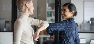 Zwei weibliche Kollegen halten sozialen Abstand