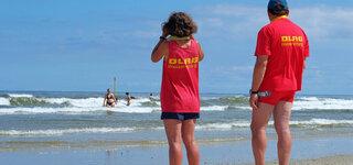Coronavirus Zwei Mitglieder der DLRG Wasserrettung stehen am Strand der Insel Spiekeroog und beobachten Schwimmer in den Wellen der Nordsee. Insel Spiekeroog