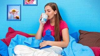 Frau mit Wärmflasche im Bett trinkt Tee