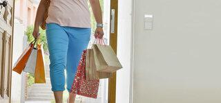 Übergewichtige Frau trägt schwere Tüten