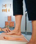 Bei einem Fersensporn helfen oft maßgefertigte Einlagen. Hier wird dazu ein Fußabdruck angefertigt