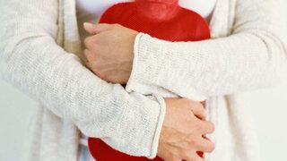Frau hält sich Wärmflasche an den Bauch