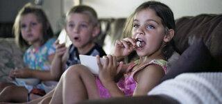 Kinder essen Fast Food vor dem Fernseher
