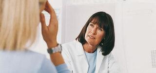 Sprechstunde Ärztin berät Patientin mit Kopfschmerzen