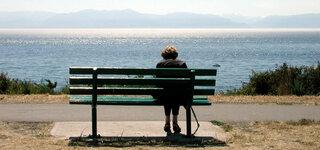 Einsame Person auf einer Bank am See