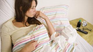 Frau liegt mit Wochenbett-Depression im Bett
