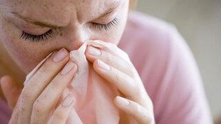 Frau beim Nase putzen