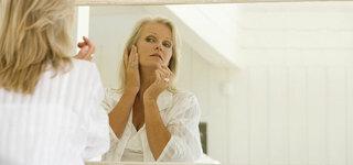 Seniorin betrachtet sich kritisch im Spiegel