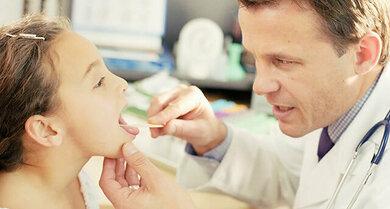 Bei einer Schwellung am Hals kontrolliert der Arzt auch Mund und Rachen