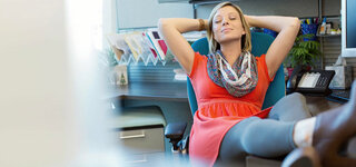 Junge Frau legt im Büro die Beine hoch