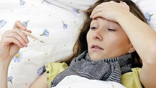 Frau mit Fieber im Bett