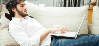 Mann liegt mit Laptop auf Sofa