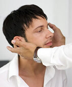 Der Arzt tastet den Hals hinter den Ohren ab