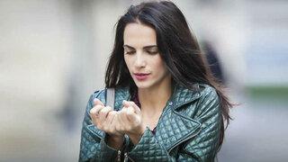 Frau schaut ihre kalten Finger an