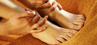 Hände halten eigene Füße