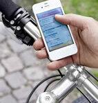 Radfahrer sucht mit seinem Smartphone und Apotheken-App eine Apotheke