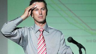 Mann am Rednerpult schwitzt vor Nervosität