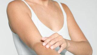 Frau cremt sich den Arm ein