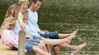 Familie lässt die Beine im Wasser baumeln