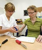 Die Ergotherapeutin macht Besteck mit Hilfe von Schaumgummi griffiger