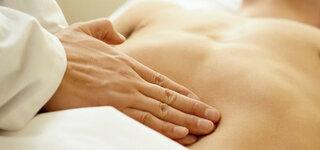 Untersuchung: Arzt tastet Bauch ab