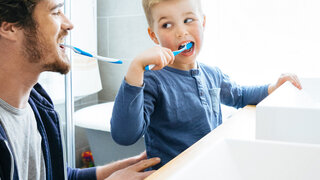 Vater und Sohn putzen Zähne