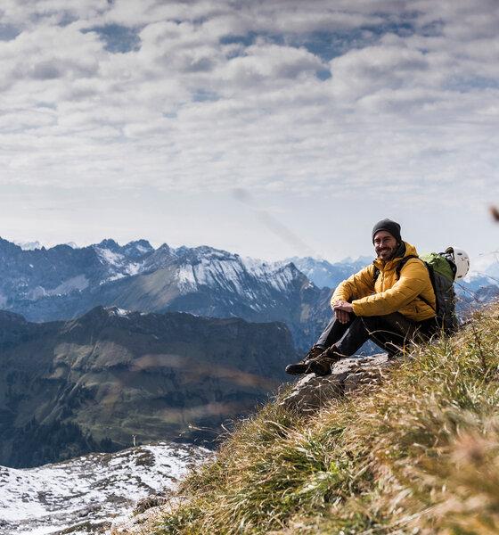 Mann sitzt auf einem Berg und genießt die Aussicht