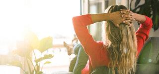 Frau sitzt auf der Couch und schaut aus dem offenem Balkonfenster