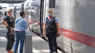 Fahrgäste sprechen mit einer Bediensteten der DB auf dem Bahnsteig vor einem ICE