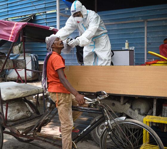 Indien: Mann auf Fahrrad bei der Tupferprobe am Straßenrand
