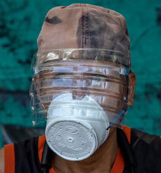 Ein Mann trägt eine provisorische Maske aus einem Styroporbecher und einen Gesichtsschutz aus einer Plastikflasche zum Schutz vor COVID-19