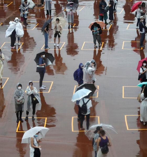 Menschen warten vor Wiedereröffnung von Tokio Disneyland im Regen