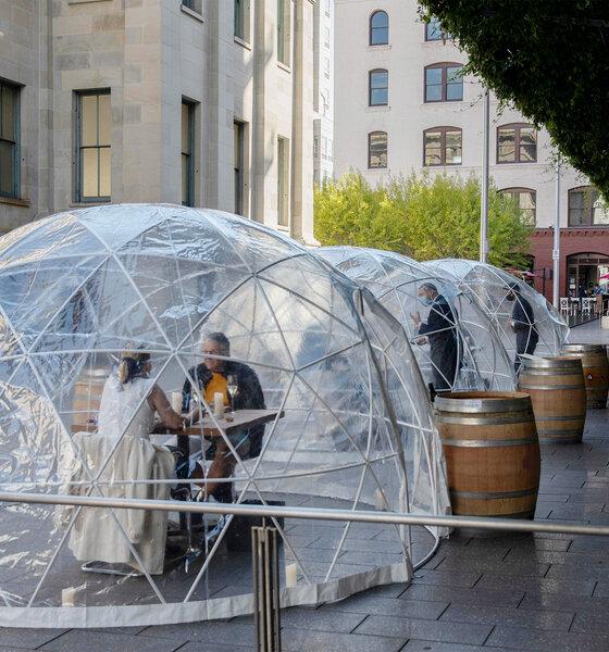 Menschen essen im transparenten, halbkugelförmigen Essbereich vor einem japanischen Restaurant