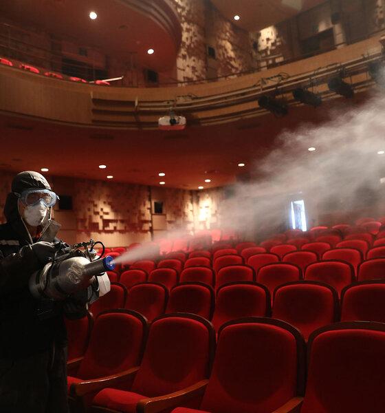 Mann mit Desinfektionsspray im Kino