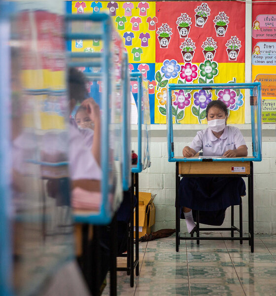 Schüler in Thailand mit Mundschutz und Plastikschutzschildern an den Schreibtischen